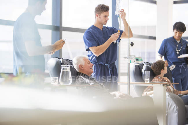 Doctors attending patients receiving intravenous infusion in hospital — Stock Photo