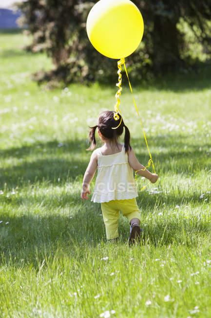 Fille portant ballon dans la cour arrière — Photo de stock