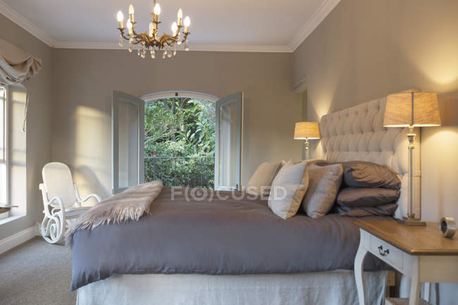 Habitación de lujo con cama contra la ventana en el interior - foto de stock