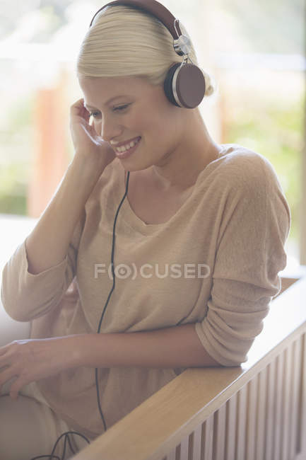 Woman listening to headphones on sofa — Stock Photo