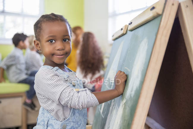 Девушка рисует на доске в классе — стоковое фото