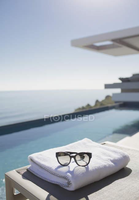 Lunettes de soleil sur serviette pliée au bord de la piscine sur patio de luxe ensoleillé avec vue sur l'océan — Photo de stock
