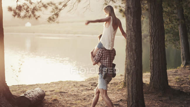 Young man carrying woman on shoulders at lakeside — Stock Photo