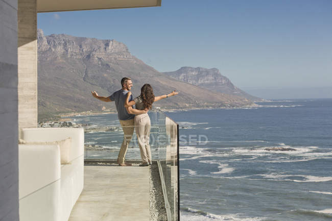 Carefree couple standing on sunny luxury balcony with ocean and mountain view — Stock Photo