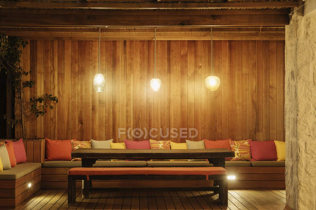 Pendant lights illuminated over patio bench with cushions — Stock Photo