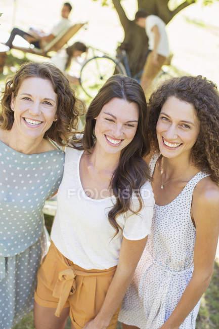 Feliz madre bella e hijas abrazando al aire libre - foto de stock