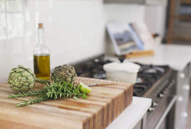 Artichauts, romarin, huile d'olive et citron vert sur planche à découper — Photo de stock