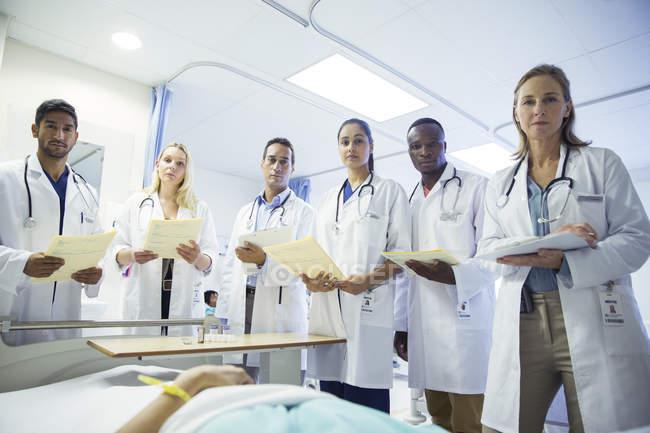 Médico y residentes examinando paciente en cama de hospital - foto de stock