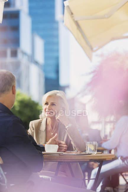 Imprenditrice che ascolta un uomo d'affari al soleggiato caffè sul marciapiede urbano — Foto stock