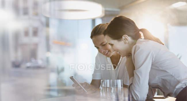 Деловая женщина текстовых сообщений с мобильного телефона в офисе — стоковое фото