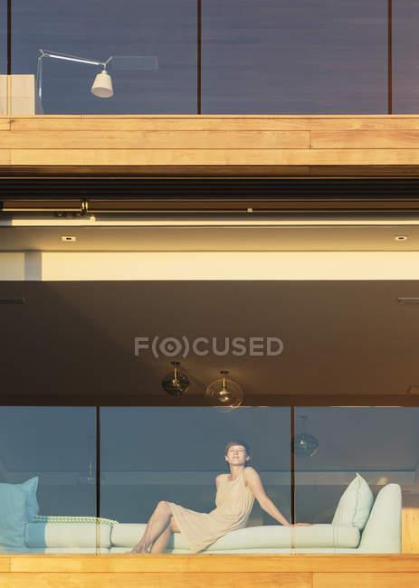 Mulher sentada na varanda de luxo ensolarada — Fotografia de Stock