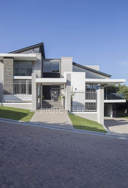 Casa moderna contra estrada sob céu azul — Fotografia de Stock