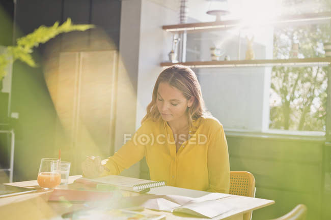 Woman drawing at sunny kitchen table — Stock Photo