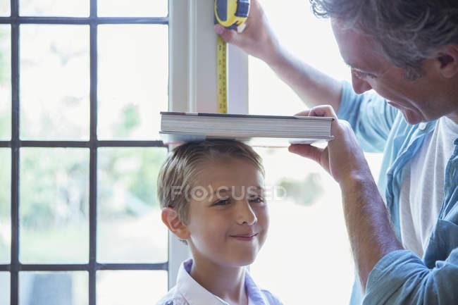 Padre misura l'altezza del figlio sul muro — Foto stock
