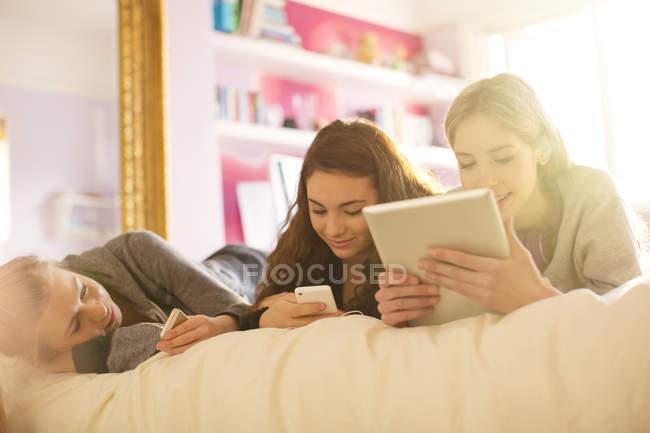 Adolescenti che utilizzano telefoni cellulari e tablet digitale sul letto — Foto stock