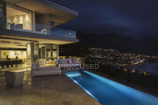 Casa di lusso illuminata vetrina esterna con piscina sul giro di notte — Foto stock
