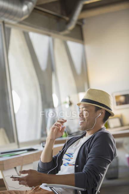 Lässige Geschäftsmann mit Freisprecheinrichtung mit Handy im Büro — Stockfoto