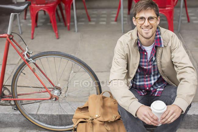 Uomo bere caffè sulla strada della città — Foto stock