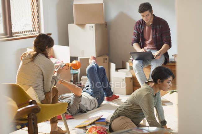 Coinquilini giovani amici in movimento in disimballaggio scatole in appartamento — Foto stock
