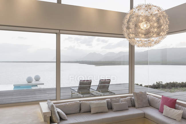 Modern luxury home showcase interior living room with chandelier and ocean view — Stock Photo