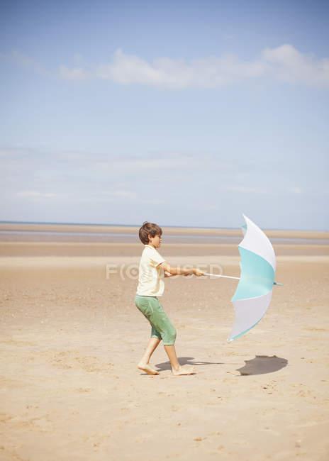 Vent en tirant le parapluie dans les mains du garçon sur la plage ensoleillée de l'été — Photo de stock
