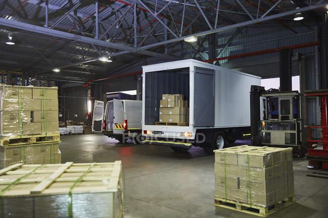 Грузовые автомобили и картонные коробки поддоны на складе дистрибуции погрузочной док — стоковое фото