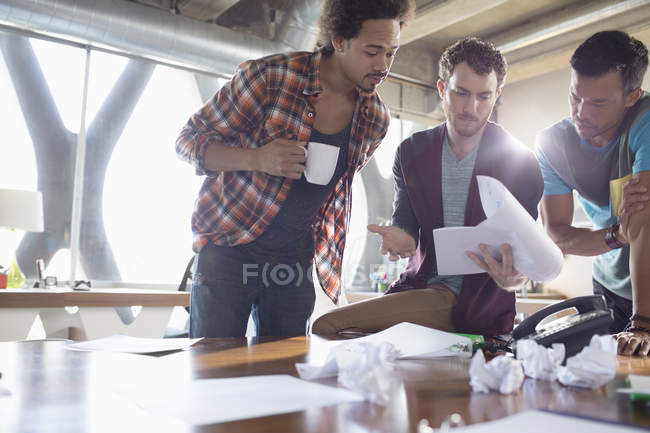 Creative businessmen reviewing paperwork in meeting — Stock Photo