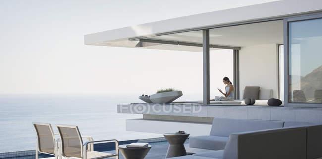 Donna seduta su un moderno e lussuoso patio esterno vetrina con vista sull'oceano — Foto stock