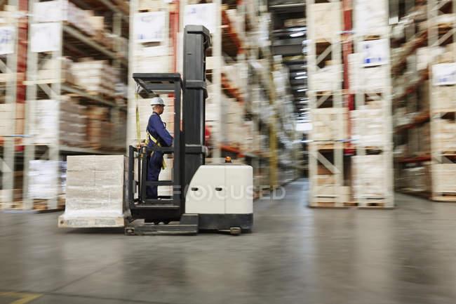 Рабочий, работающий на вилочном погрузчике, перевозящий поддон коробок на складе дистрибуции — стоковое фото