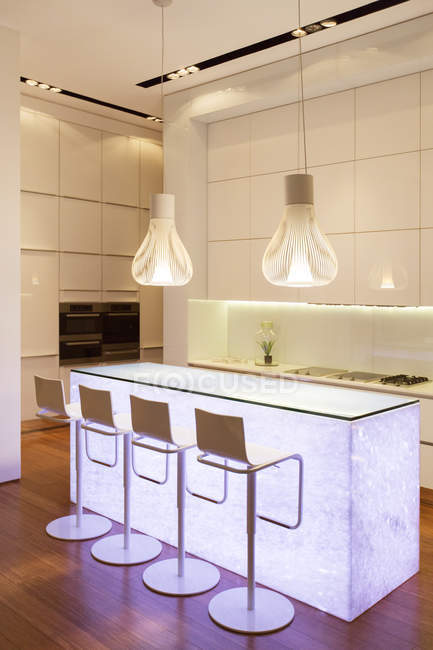 Bar stools and light features in modern kitchen — Stock Photo