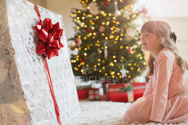 Girl smiling in anticipation at large Christmas gift near Christmas tree — Stock Photo