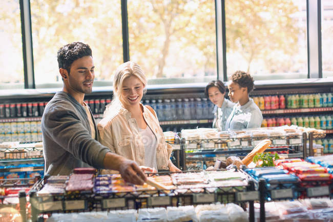 Smiling young couple grocery shopping in market — Stock Photo