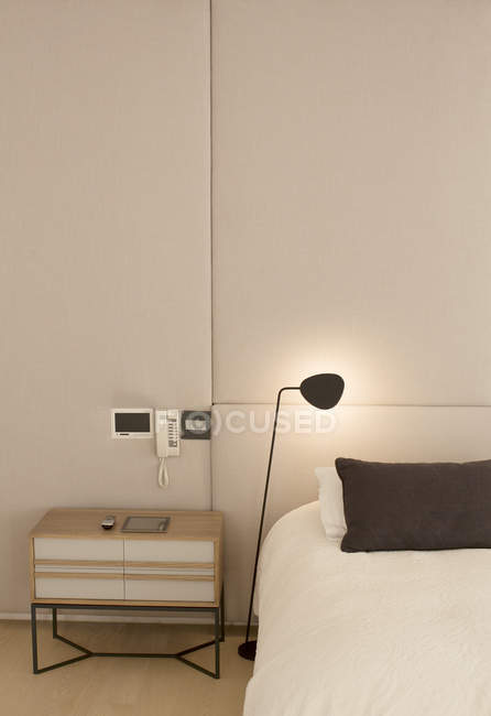 Illuminated lamp over bed — Stock Photo
