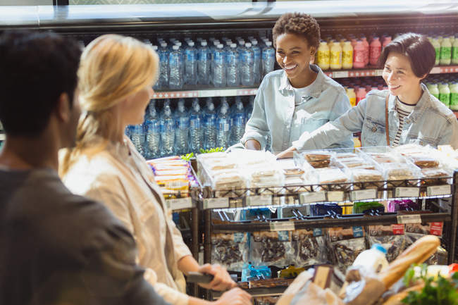 Young friends talking in grocery store market — Stock Photo