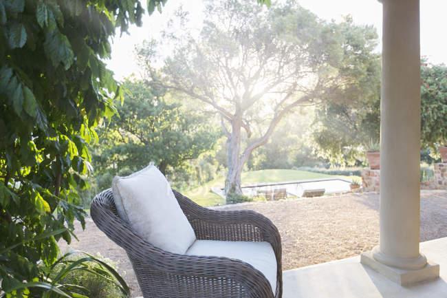 Poltrona in vimini sul tranquillo patio — Foto stock