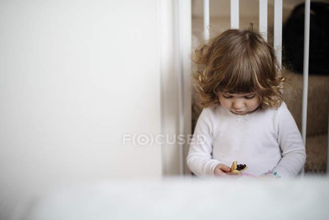 Девушка ест закуску на лестнице — стоковое фото