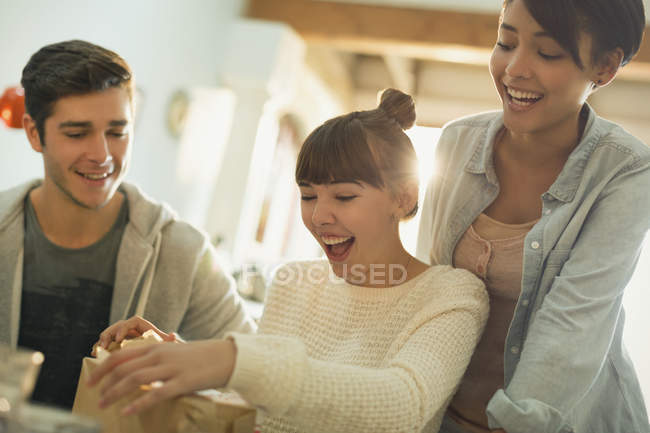 Young friends celebrating birthday opening gift — Stock Photo