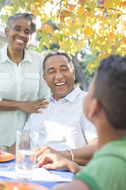 Abuelos y nieto riendo en la mesa del patio - foto de stock