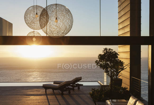 Patio of modern house overlooking ocean at sunset — Stock Photo