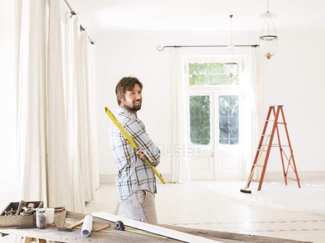 Людина з видом житлової площі біля будівельних матеріалів — стокове фото