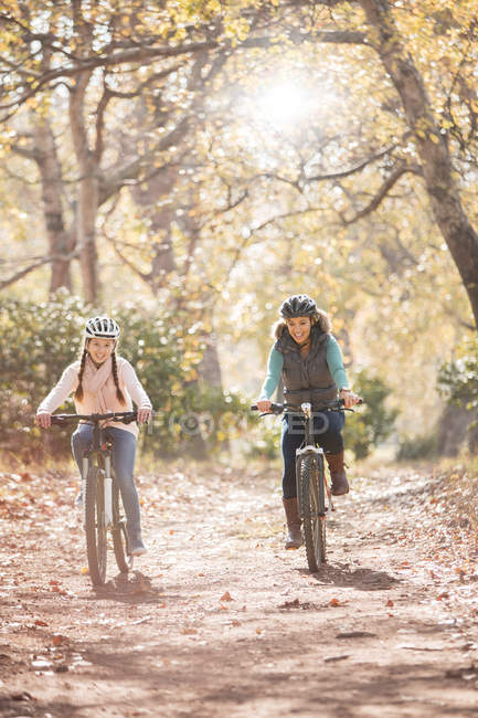 Mother and daughter bike riding on path in woods — Stock Photo