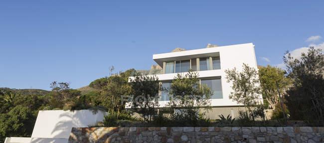 Bäume um sonnige moderne moderne Luxus Weißen Hause Schaukasten außen — Stockfoto