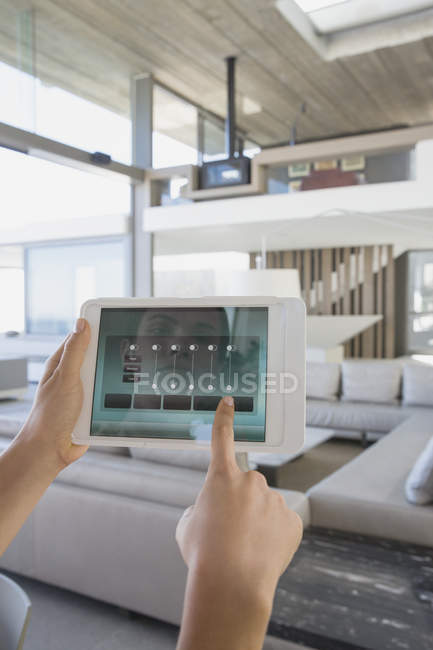 Personal perspective woman with digital tablet setting digital climate control in modern, luxury home showcase interior living room — Stock Photo