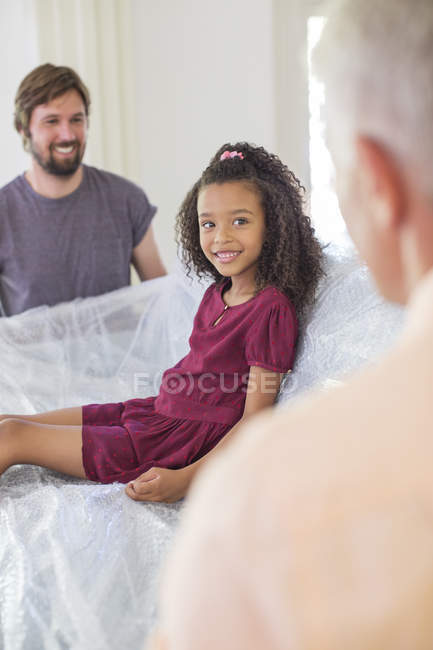 Family lifting couch with young girl sitting on top — Stock Photo