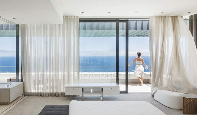 Жінка на сучасних балкон з видом на океан — стокове фото