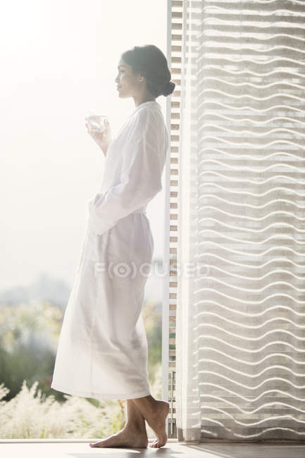 Женщина в Халат питьевой воды в открытых дверей — стоковое фото