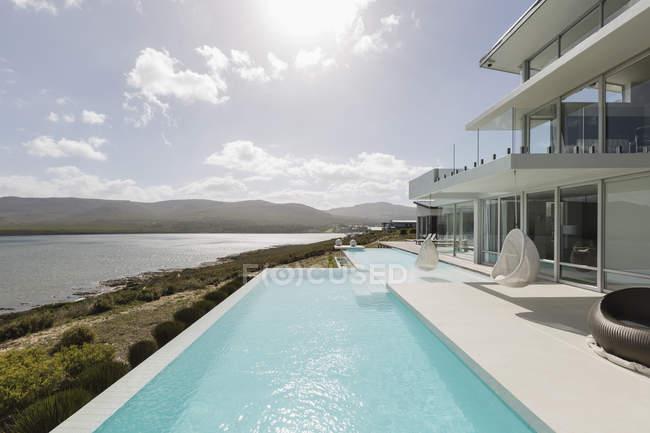 Sunny, tranquilla casa di lusso moderna vetrina esterna con piscina a sfioro e vista sull'oceano — Foto stock