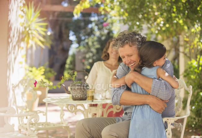 Happy caucasian grandfather and granddaughter hugging outdoors — Stock Photo