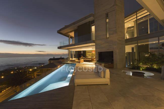 Iluminada casa de luxo vitrine exterior e piscina de colo infinito com vista para o mar — Fotografia de Stock