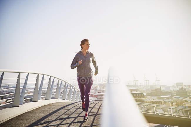 Бегунья бежит по солнечному городскому пешеходному мосту на рассвете — стоковое фото